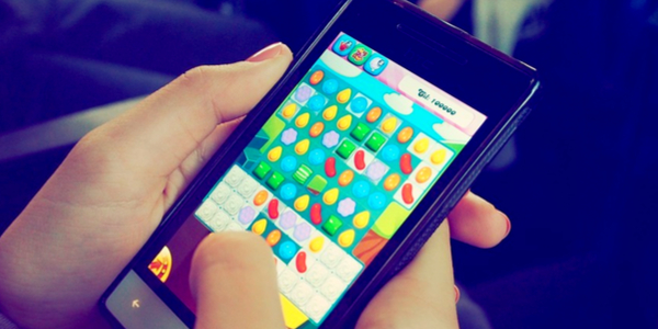Woman holding phone and playing candy crush